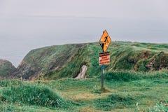 I segnali di pericolo di superficie sdrucciolevole e dei bordi non protetti al Dunquin iconico harbour i dintorni del pilastro in fotografia stock