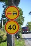I segnali stradali che sorpassano è vietato, la restrizione della velocità massima di 40 chilometri contro la strada Fotografie Stock Libere da Diritti