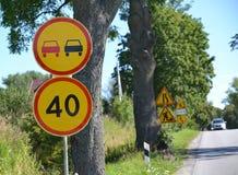 I segnali stradali che sorpassano è vietato, la restrizione della velocità massima di 40 chilometri contro la strada Fotografia Stock