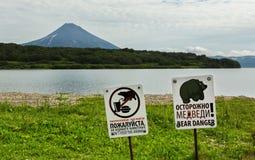 I segni avvertono del pericolo dei turisti di riunione con riguarda il fondo del vulcano del lago e di Ilyinsky Kurile Fotografia Stock Libera da Diritti