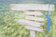 I segni di legno vuoti bianchi rustici con le stelle marine blu sopra l'oceano verde fresco innaffiano Immagine Stock