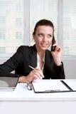 I segni femminili documenta la seduta alla tavola e la conversazione sul telefono Fotografia Stock