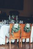 I segni governano e sposa nelle sedie intorno alla tavola di nozze Fotografia Stock Libera da Diritti