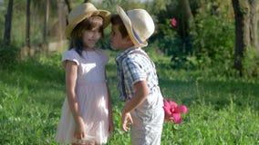 I segreti dei bambini, ragazzino bisbiglia in orecchio alla ragazza ed a tenere il fiore lei indietro nel parco dell'estate archivi video
