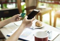 I selektivt av mobiltelefonen rymde vid assistenten och den suddiga kreditkorten på vänstersidahanden, för att shoppa direktanslu arkivfoto