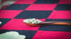 I semi di girasole sul cucchiaio di legno, hanno messo sopra un fondo rosso Immagini Stock Libere da Diritti
