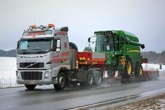 I semi di Volvo FH16 trasportano John Deere Combine in tempo piovoso Immagini Stock