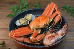 Marine products helping of various kinds of dishes. I served an abalone, a deep red snow crab, red prawns to a colander Royalty Free Stock Images