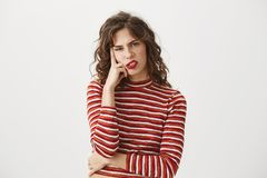 I am sick of you. Indoor shot of bored and disgusted attractive young woman leaning on finger and looking with. Disrespect or boredom at camera, standing over Stock Photos