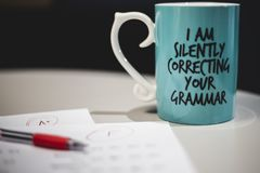 `I am silently correcting your grammar` coffee mug royalty free stock image