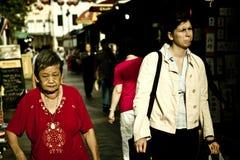 I Singapore bor lokaler och utländska migranter nära arkivbild