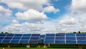 I sistemi di tracciamento del pannello solare con le nuvole infuriano la venuta qui Fotografia Stock