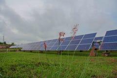 I sistemi di tracciamento del pannello solare con le nuvole infuriano la venuta qui Immagini Stock