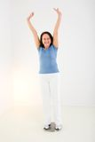 I slim down. Woman dressed sportswear standing on bathroom scales. She looks very happy. Front view Royalty Free Stock Photography