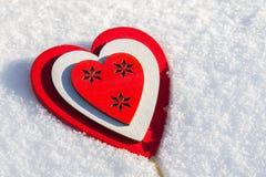 I snölögnerna en röd hjärta som göras av trä Mall för ett feriekort med en vit textur och fritt utrymme för text Arkivbilder