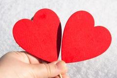 I snölögnerna en röd hjärta som göras av trä Mall för ett feriekort med en vit textur och fritt utrymme för text Royaltyfria Bilder