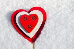 I snölögnerna en röd hjärta som göras av trä Mall för ett feriekort med en vit textur och fritt utrymme för text Fotografering för Bildbyråer