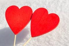 I snölögnerna en röd hjärta som göras av trä Mall för ett feriekort med en vit textur och fritt utrymme för text Arkivbild
