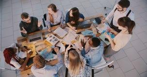 I soci commerciali felici cooperano alla tavola moderna dell'ufficio, creano le idee con il CEO maschio ed il punto di vista supe archivi video
