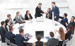 I soci commerciali stringono le mani ai colloqui vicino alla tavola rotonda Fotografia Stock