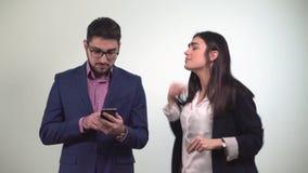 I soci commerciali un uomo esamina lo smartphone e la ragazza dopo che il ballo ottiene i soldi vinti nella scommessa dal stock footage