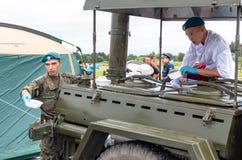 I soldati curano la gente con il porridge del grano saraceno cucinato in una cucina di campo militare sull'esercito russo di most fotografie stock libere da diritti