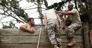 I soldati maschii che assistono il loro gruppo si accoppiano per scalare una parete di legno 4k video d archivio