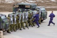 I soldati tedeschi della polizia militare difende un'area contro il ruolo che gioca i dimostratori immagini stock libere da diritti