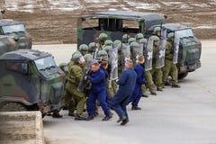 I soldati tedeschi della polizia militare difende un'area contro il ruolo che gioca i dimostratori immagini stock