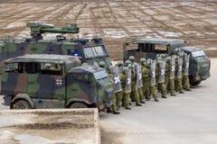 I soldati tedeschi della polizia militare difende un'area contro il ruolo che gioca i dimostratori fotografia stock