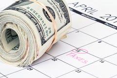 I soldi dei contanti rotolano su un calendario Fotografia Stock Libera da Diritti