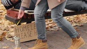 I soldi di lancio della giovane donna dentro possono, aiutando il povero senza tetto congelato equipaggiano, la carità video d archivio