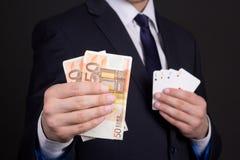 I soldi e quattro carte degli assi dentro equipaggiano le mani Immagini Stock Libere da Diritti