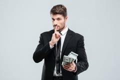 I soldi giovani bei e la rappresentazione della tenuta dell'uomo d'affari fanno tacere il segno Fotografia Stock Libera da Diritti
