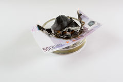 I soldi in un portacenere bruciano Fotografie Stock