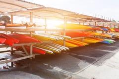 I solljus förlade röda, gula och vita kajaker uppochnervänt på metalllagringskuggar Lagerförd kanot i Brest, Frankrike 28 Maj 201 Arkivfoton