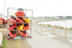 I solljus förlade röda, gula och vita kajaker uppochnervänt på metalllagringskuggar Lagerförd kanot i Brest, Frankrike 28 Maj 201 Royaltyfria Foton