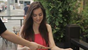 I sommar för kvinna med telefonen i kafé kommer med uppassaren menyn stock video