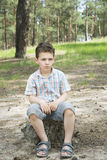 I sommar i en pinjeskog på en trädstubbe sitter den ledsna pojken Arkivbild
