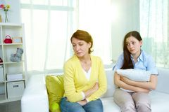 I am sorry. Photo of offended women sitting on sofa with her teenage daughter being sorry for what she did Stock Image