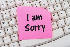 I am sorry. A close-up of a keyboard with pink sticky note with text I am Sorry Royalty Free Stock Photos