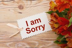 I am Sorry Gift Tag with Flowers. Some lilies on weathered wood with a gift tag with text I am Sorry Royalty Free Stock Photos