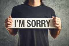 I am sorry message. Man holding I am sorry message on white board. remorse concept Stock Photography