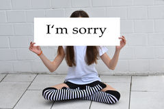 I am sorry. Teenage girl  hidden behind a white board with I'm sorry message Stock Images