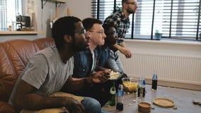 I sostenitori maschii della corsa mista guardano gli sport sulla TV 4K I fan celebrano la vittoria di scopo che tiene il cuscino  Fotografia Stock