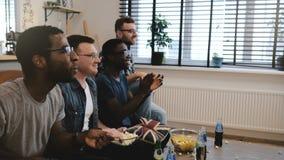 I sostenitori maschii della corsa mista guardano gli sport sulla TV 4K I fan celebrano la vittoria di scopo che tiene il cuscino  Immagine Stock