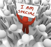 I Am Special Man Holding Sign Standing Out Crowd Different Uniqu. I Am Special words on a sign held by a man in a crowd standing out as different, unique Royalty Free Stock Images