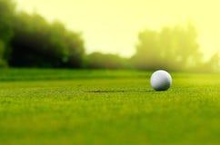 I spela golfboll i hål Arkivbild