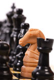 I am a spy. The light knight stands among dark chess-pieces Royalty Free Stock Images