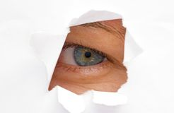 I spy. A womans eye looking trough a cut paper hole Stock Photos